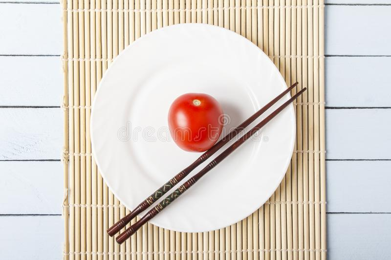 Ripe red tomato and chopsticks on white plate. Top view on wooden table with bamboo mat. Vegetarian food concept stock photo