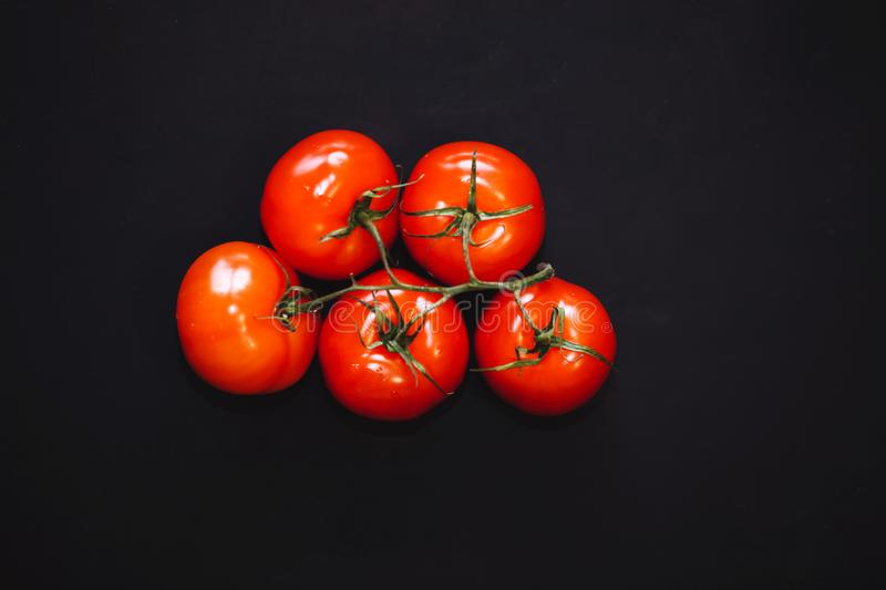 Ripe red tomatoes on black background, top view. The whole vegetable. closeup stock photos