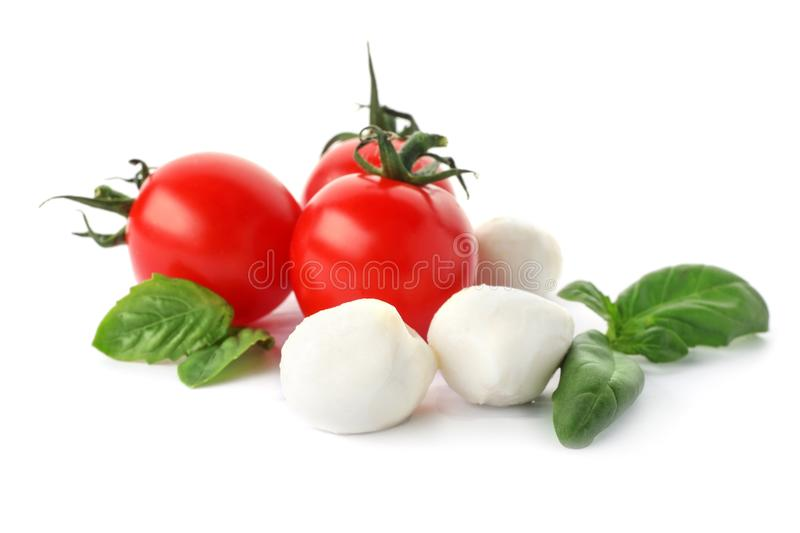 Ripe red tomatoes, mozzarella cheese balls. And basil on white background royalty free stock photo