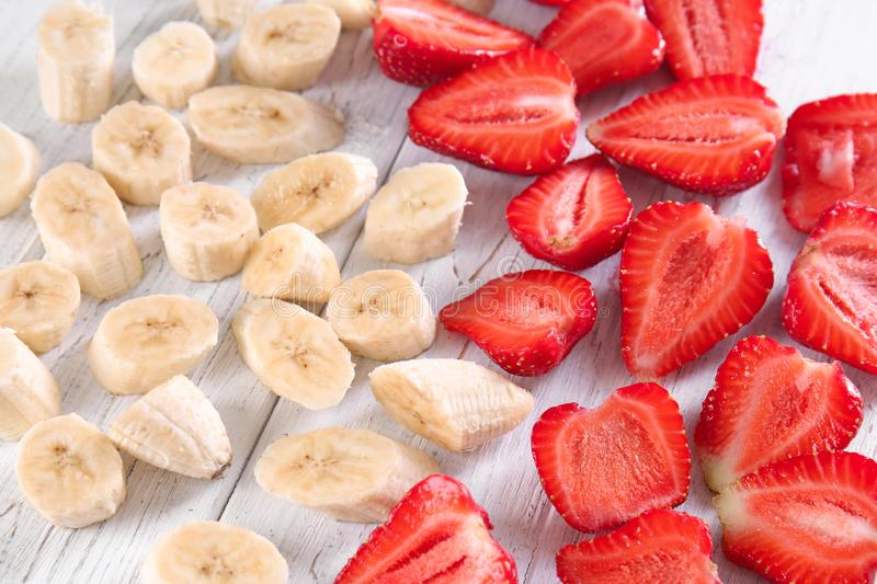 Ripe sliced strawberries and bananas on light wooden background stock images