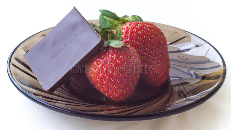 Ripe strawberries and chocolate on a glass plate royalty free stock image