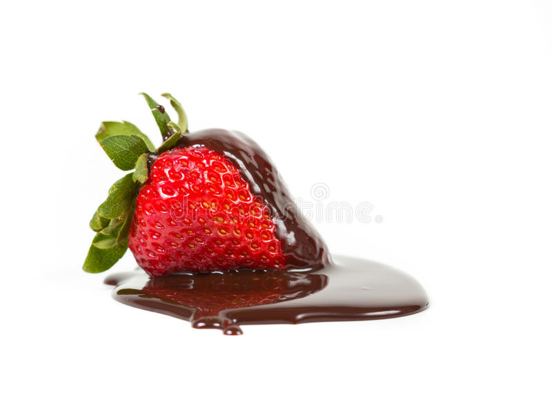 Ripe strawberry in a pool of chocolate syrup. Isolated on a white background stock images