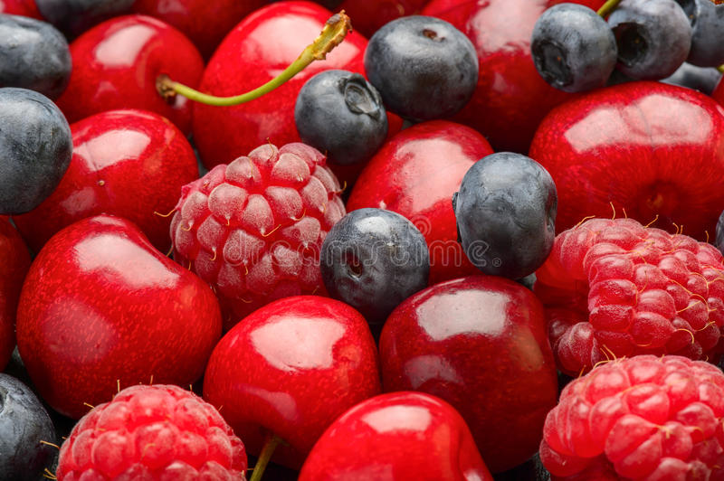 Ripe summer berries (blueberries, raspberries and cherries) as background. royalty free stock photos