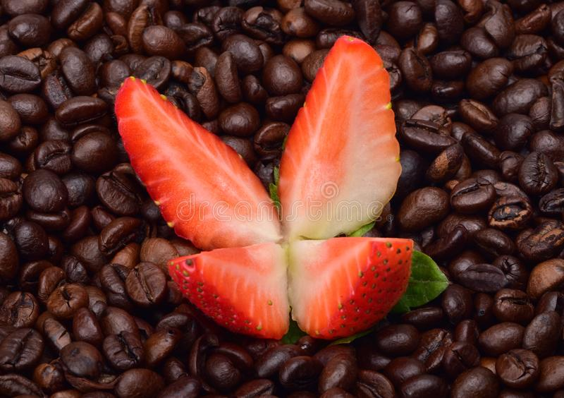 Ripe summer strawberry, cut into four parts, against the background of fragrant beans of fresh coffee. Ripe summer strawberry, cut into four parts, against the stock photo