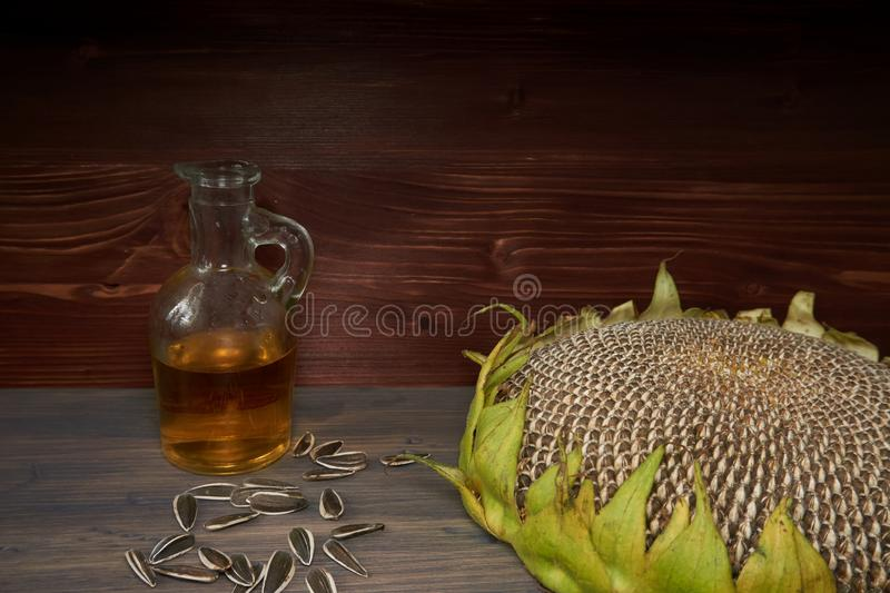Ripe sunflowers seeds and bottle of sunflower oil. Ripe sunflowers seeds on the flower head and bottle of sunflower oil on a brown rustic wood background stock images