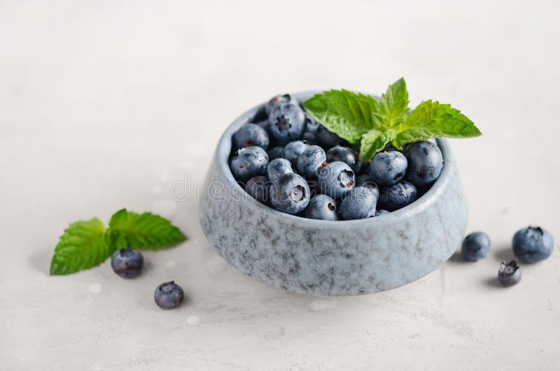 Ripe sweet blueberries in blue bowl on a gray concrete background. Ripe sweet blueberries in blue bowl on a gray concrete background, selective focus stock photos
