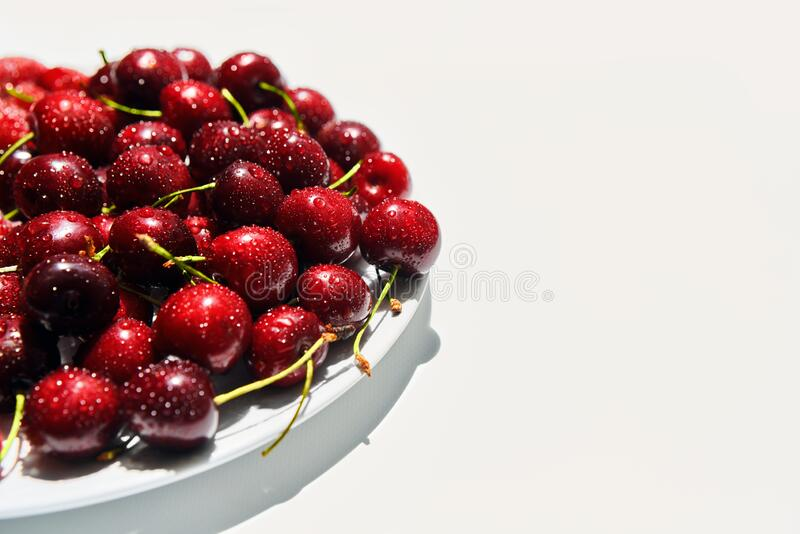 Ripe sweet cherries on plate isolated on white background with copy space royalty free stock photography