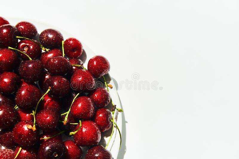 Ripe sweet cherries on plate isolated on white background with copy space royalty free stock photos