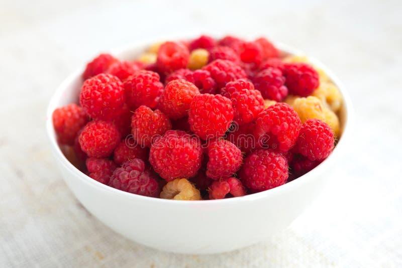 Ripe sweet raspberries in bowl. On cloth stock photo