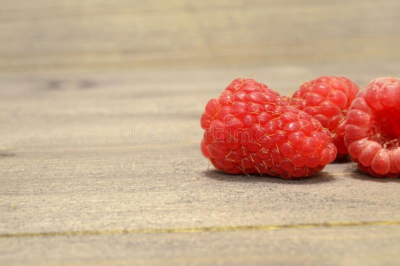 Ripe Sweet Raspberries on the Wooden Table Against the Heap of Summer Fruits and Berries stock image