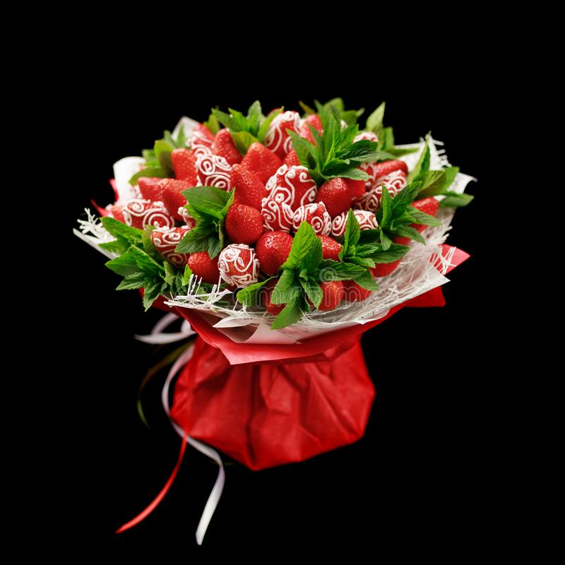 Ripe tasty strawberries decorated with white chocolate with fresh mint leaves in the form of bouquet isolated on black background royalty free stock image