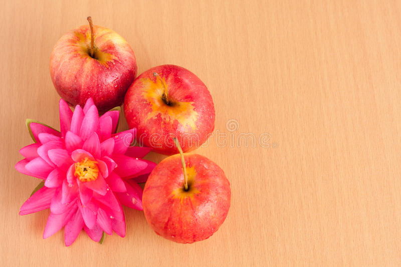Ripe three red apple with artificial flower. On plywood backgroun royalty free stock photography