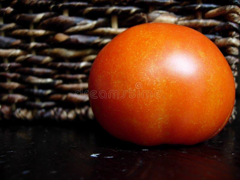 Ripe tomato with brown woven basket stock photo