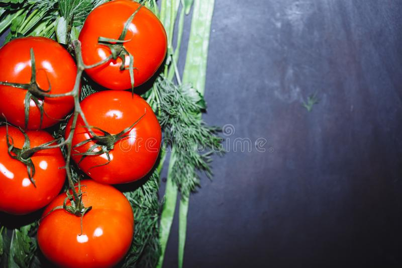 Ripe tomatoes with herbs on black background. The whole vegetable stock image