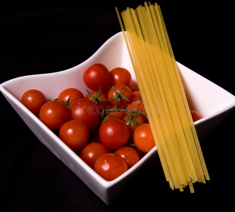 Ripe tomatoes and pasta. Bowl of ripe red tomatoes with dry pasta noodles against black background stock photo