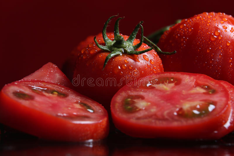 Tomatoes under water drops, red background royalty free stock image
