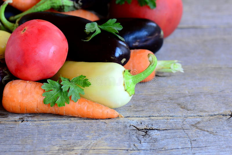 Ripe vegetables assortment. Organic eggplants, tomatoes, carrots, peppers, parsley on a vintage wooden table. Garden vegetables royalty free stock photo