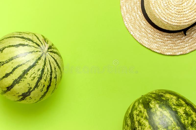 Ripe watermelon berry, summer straw hat on green background top view flat lay copy space. Green Striped Whole Watermelon. Summer stock image