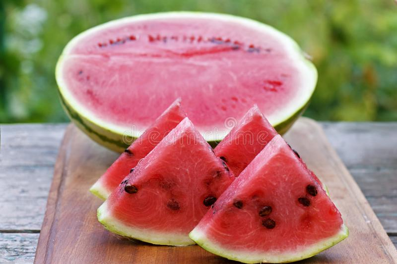 Ripe watermelon cut into slices on a wooden board stock images
