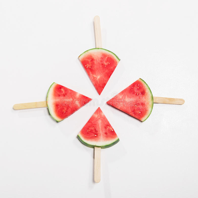 Ripe watermelon slices on wooden popsicle sticks. Top view of ripe watermelon slices on wooden popsicle sticks royalty free stock photography