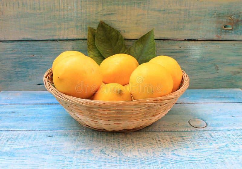 Ripe yellow lemons in a basket royalty free stock photos