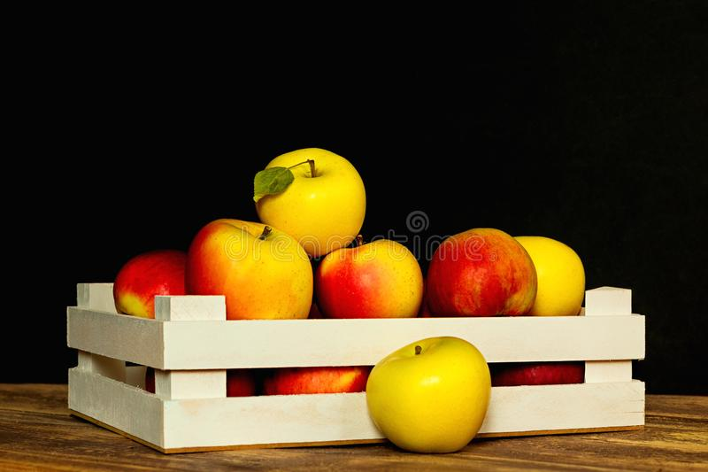 Ripe yellow and red apples in wooden box with space for text isolated on a black background. Apples in crate royalty free stock photo