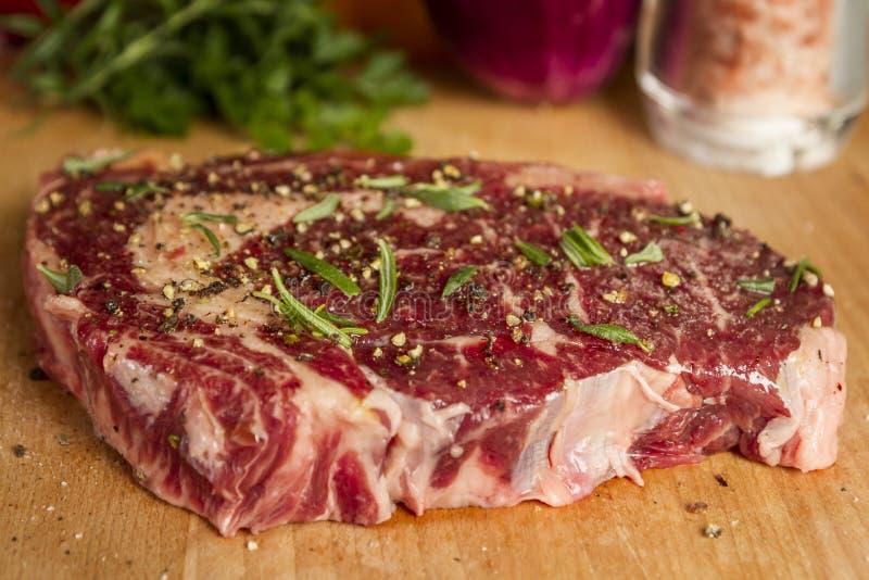 Ripened kryddade ögat för nötköttstödet eller entrecôtebiff på träsnittbrädet som var förberett för att laga mat fotografering för bildbyråer