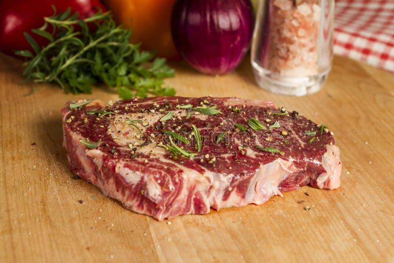 Ripened kryddade ögat för nötköttstödet eller entrecôtebiff på träsnittbrädet som var förberett för att laga mat royaltyfri bild