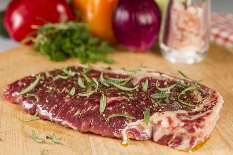 Ripened kryddade nötköttrumpan eller striploinbiff på träsnittbrädet som var förberett för att laga mat fotografering för bildbyråer
