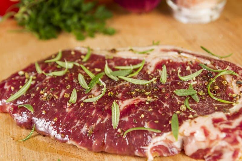 Ripened kryddade nötköttrumpan eller striploinbiff på träsnittbrädet som var förberett för att laga mat royaltyfri foto