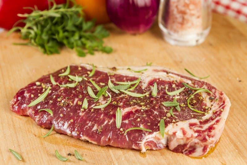 Ripened kryddade nötköttrumpan eller striploinbiff på träsnittbrädet som var förberett för att laga mat arkivfoto