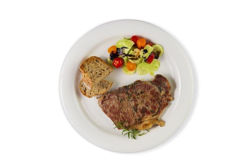 Ripened kryddade nötköttrumpan, eller striploinbiff som lagades mat på den vita plattan med sallad och hemmet, gjorde bröd royaltyfri fotografi