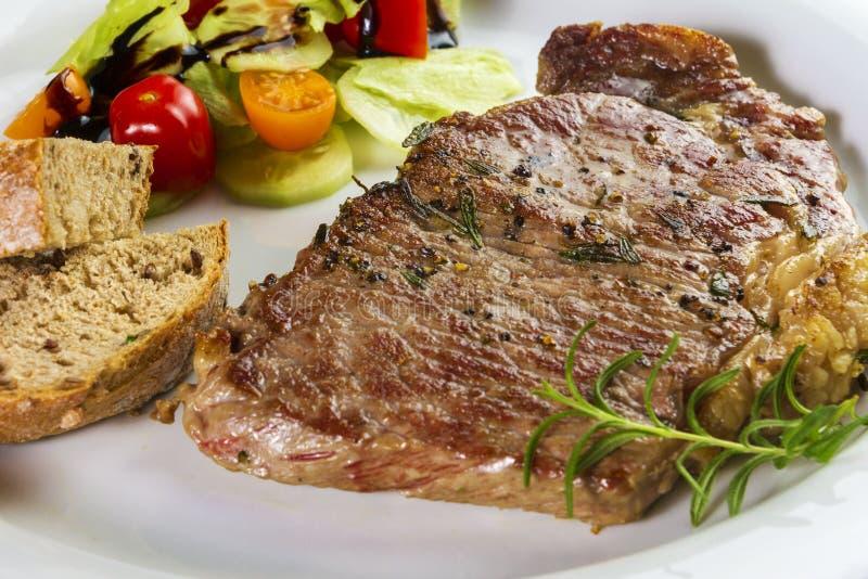 Ripened kryddade nötköttrumpan, eller striploinbiff som lagades mat på den vita plattan med sallad och hemmet, gjorde bröd arkivfoton
