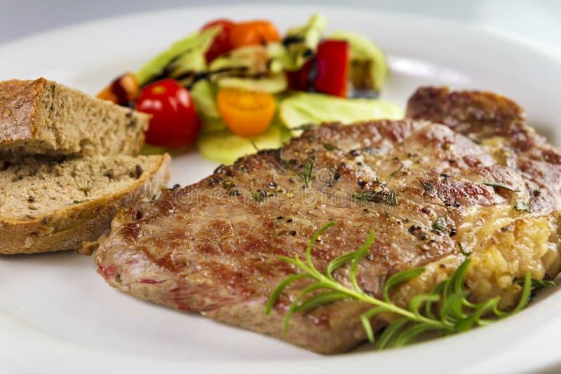 Ripened kryddade nötköttrumpan, eller striploinbiff som lagades mat på den vita plattan med sallad och hemmet, gjorde bröd arkivbilder