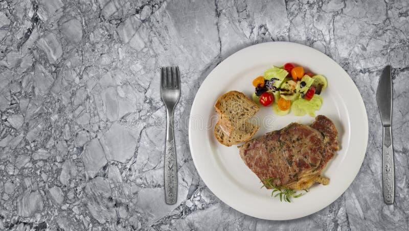 Ripened kryddade nötköttrumpan, eller striploinbiff som lagades mat på den vita plattan med sallad och hemmet, gjorde bröd arkivbild