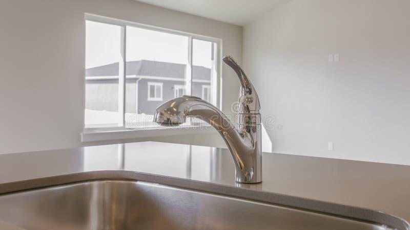 Ripiano brillante della cucina di panorama con il lavandino e rubinetto dentro una nuova casa immagine stock libera da diritti