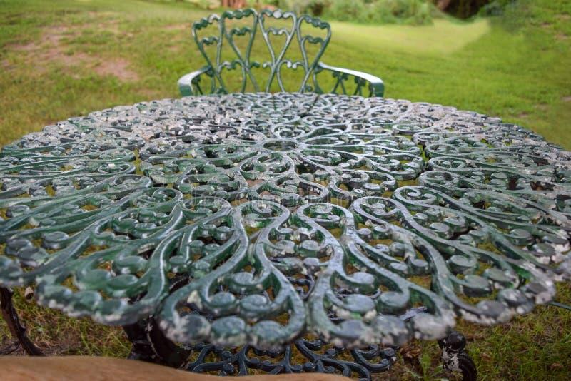 Ripiano del tavolo complesso ornato del ghisa in un giardino fotografia stock libera da diritti