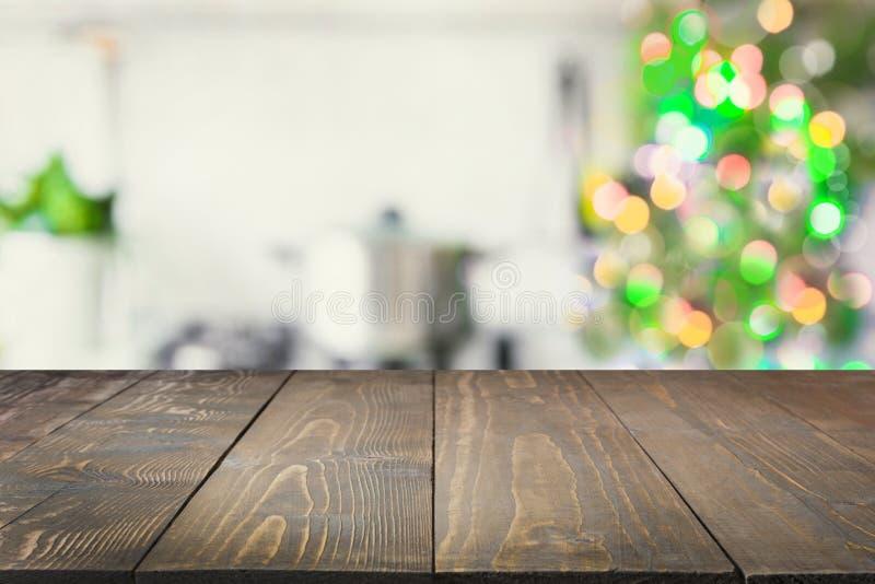 Ripiano del tavolo di legno vuoto per i prodotti dell'esposizione e cucina vaga con l'albero di Natale come fondo immagini stock