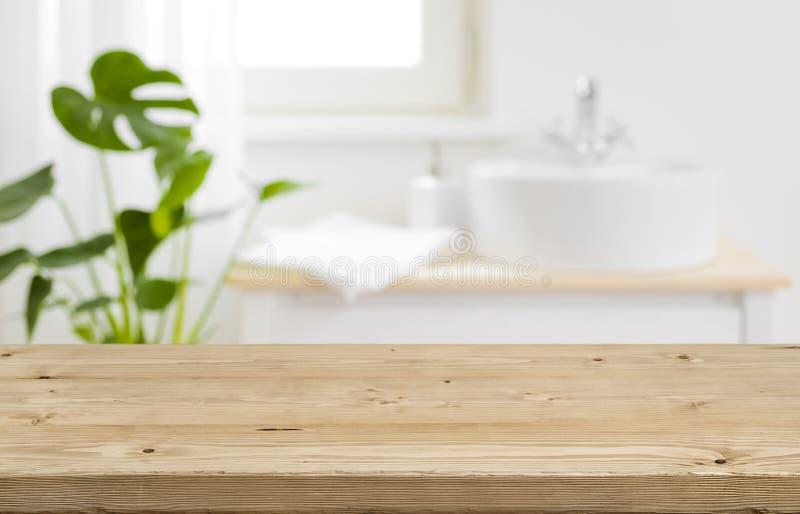 Ripiano del tavolo vuoto per l'esposizione del prodotto con il fondo vago dell'interno del bagno fotografia stock libera da diritti