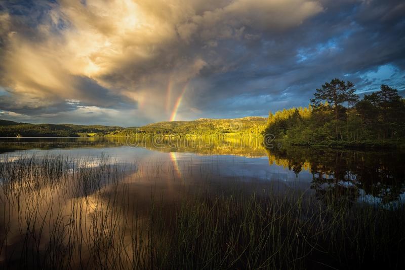 Riple rainbow observed above Jonsvatnet lake near Trondheim, sunset light after stormy day, summer in Norway stock image