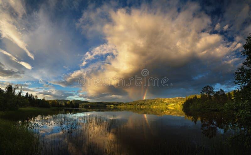 Riple regnbåge som observeras ovanför Jonsvatnet sjön nära Trondheim, solnedgångljus efter den stormiga dagen, sommar i Norge arkivfoton