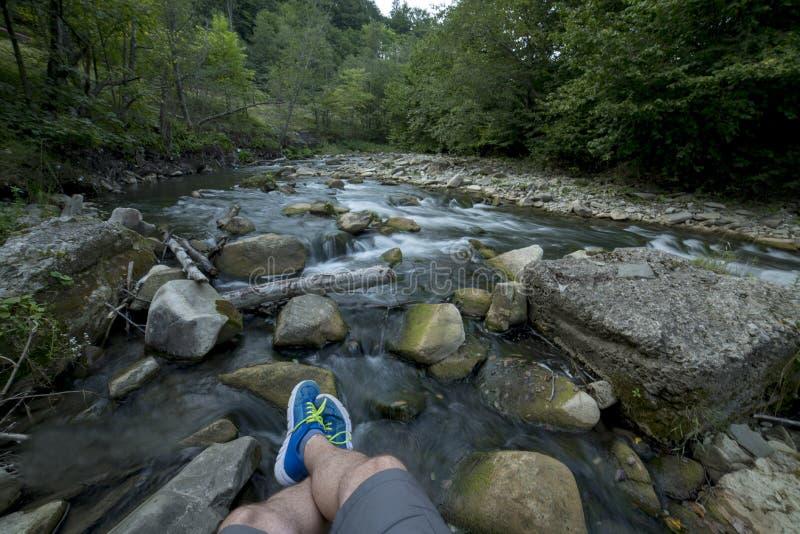 Riposando sulle rocce vicino ad un fiume fotografia stock