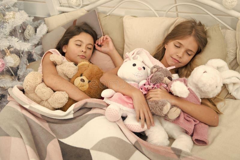 Riposarsi durante le vacanze invernali Dormire bambini I bambini dormono sull'albero di Natale Ragazzine distese a letto con fotografia stock libera da diritti