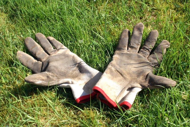Riposi dopo duri lavori - 2 guanti che godono del sunbath fotografie stock