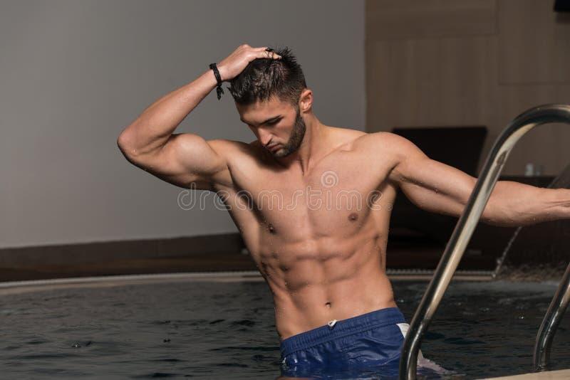 Riposo dell'uomo rilassato sul bordo della piscina fotografie stock