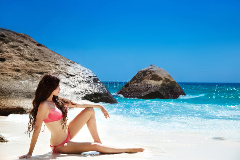 Riposo di modello del bikini sulla spiaggia tropicale Ritratto all'aperto del damerino fotografia stock