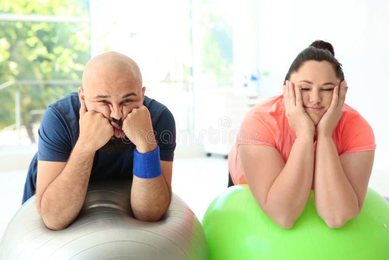 Riposo di peso eccessivo stanco della donna e dell'uomo fotografie stock