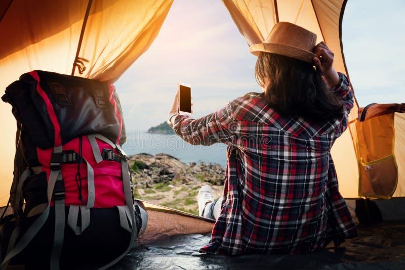 Riposo e selfie della donna dei pantaloni a vita bassa nella tenda immagini stock libere da diritti