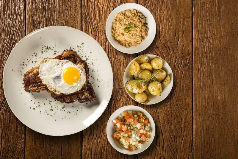 Rippe von Schweinefleisch mit Ei und Speck, begleitet mit rustikalem Kartoffel-, Essigsoße- und Maismehl stockfoto
