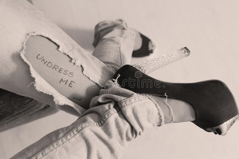 Ripped jeans with written message. Girl wearing ripped blue jeans and high heels, written message on her leg stock image